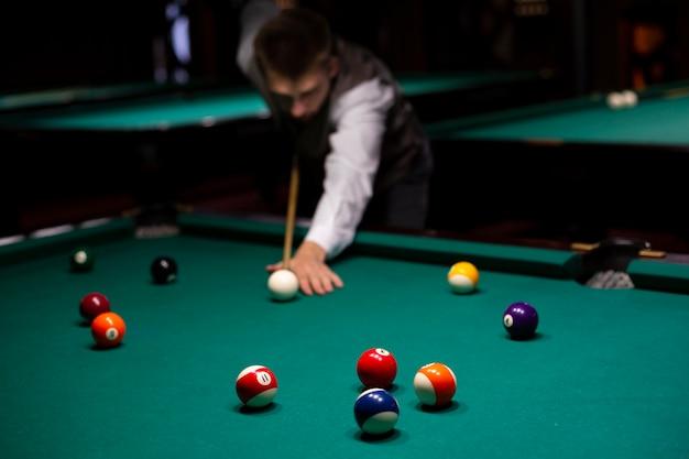 Medium shot guy with pool cue playing billiard