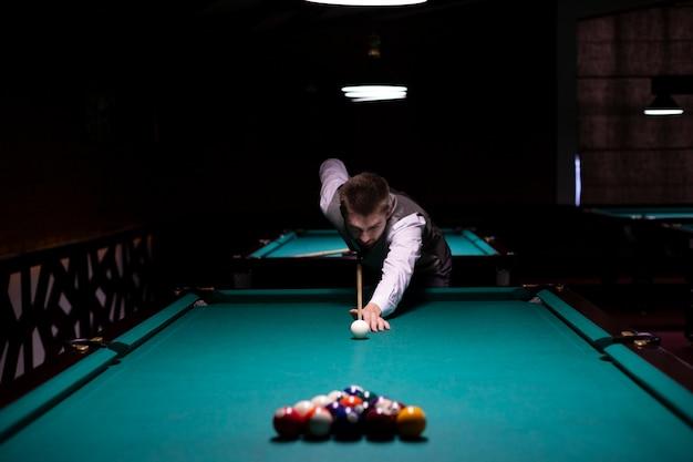 Medium shot guy with suit playing billiard