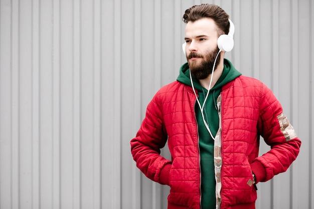 Medium shot guy with white headphones looking away