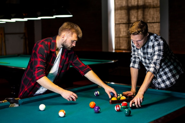 Medium shot guys arranging pool balls