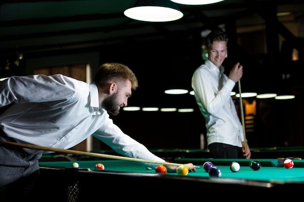 Medium shot guys playing billiard together