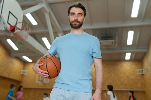 Medium shot gym teacher holding basket ball