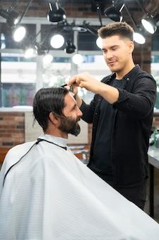 Medium shot hairdresser combing hair
