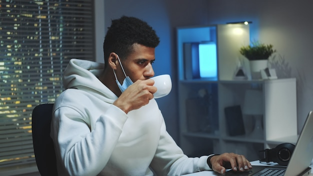 Medium shot of handsome multiracial man drinking a cup of coffee and working on computer at night