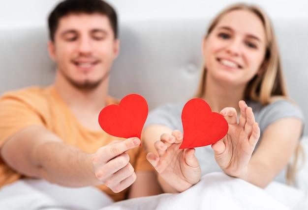 Medium shot happy blurred couple holding heart shaped paper