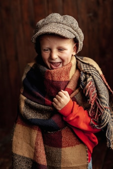 Medium shot happy boy with hat and scarf