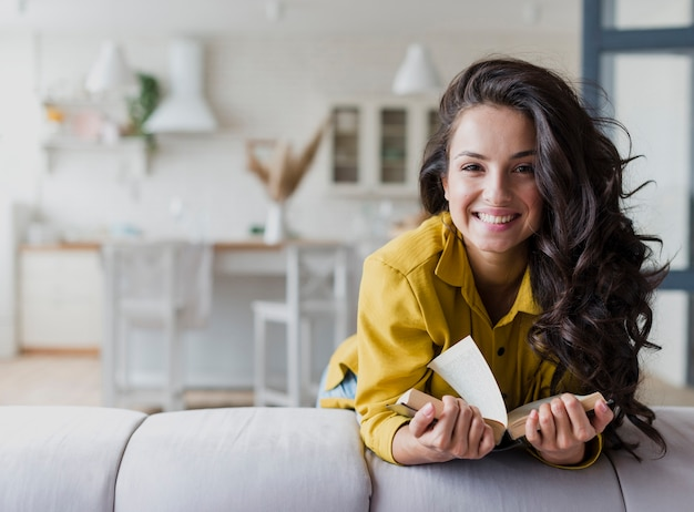 Medium shot happy brunette woman with book