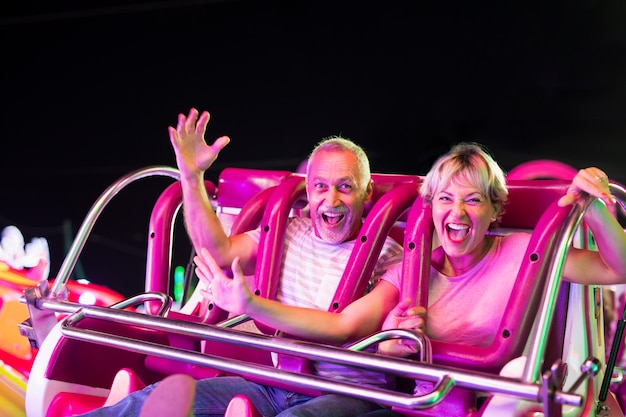Medium shot happy couple in amusement ride