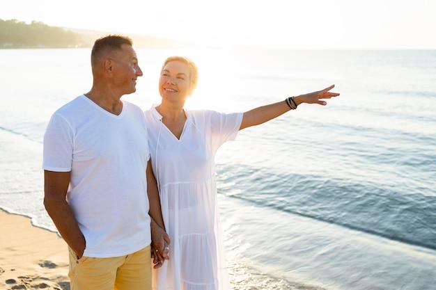Средний снимок счастливая пара на берегу моря
