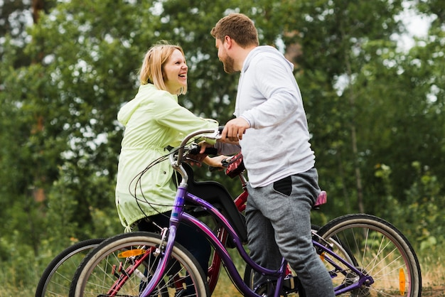 Medium shot of happy couple on bicycles