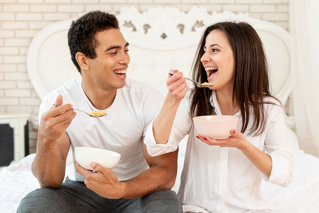 Medium shot happy couple eating cereals together