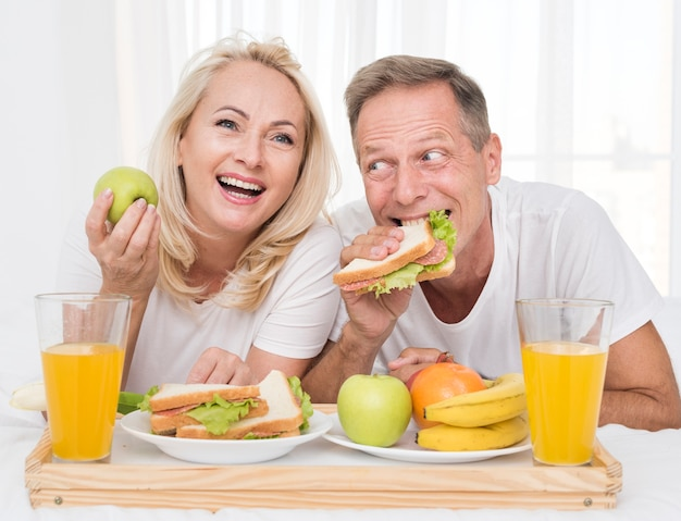 Medium shot happy couple eating healthy together