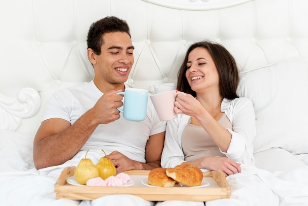 Medium shot happy couple having breakfast in bed