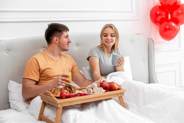 Medium shot happy couple having breakfast in bedroom