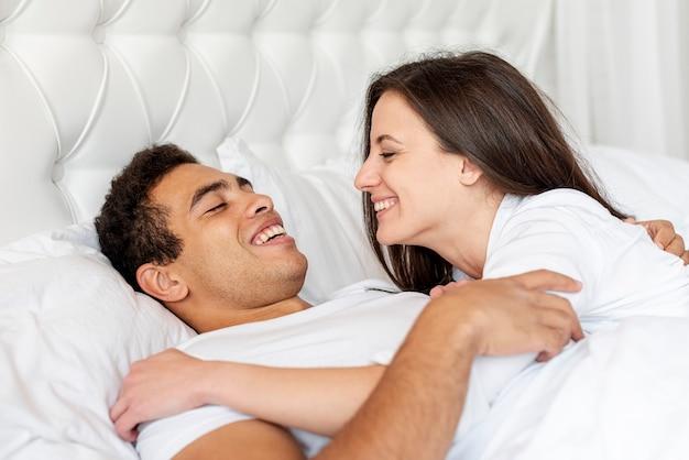 一緒にベッドでミディアムショット幸せなカップル