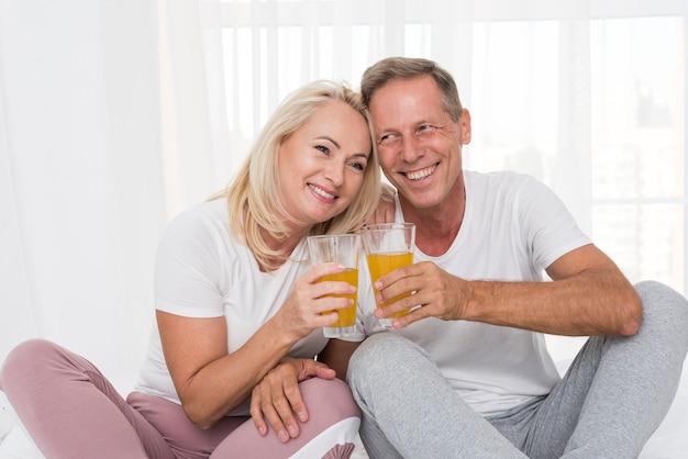 Medium shot happy couple making a toast with juice