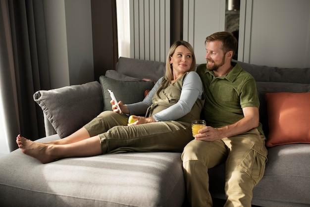 Средний снимок счастливая пара, сидящая на диване