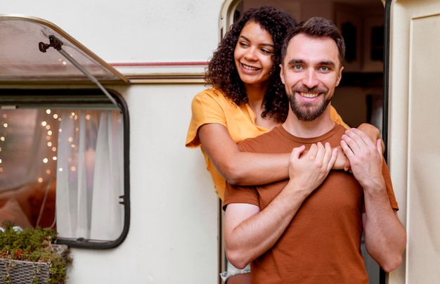 Medium shot of happy  couple standing in front of camper van