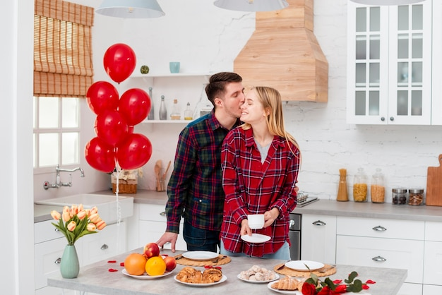 Medium shot happy couple standing in the kitchen