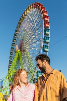 Medium shot happy couple with carnival wheel