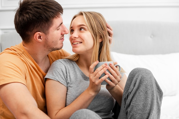 Medium shot happy couple with coffee in bed