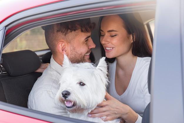 Средний снимок счастливая пара с милой собакой