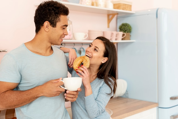 Medium shot happy couple with doughnut and cup