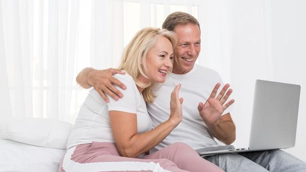 Medium shot happy couple with laptop waving