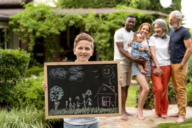 ミディアムショットの幸せな家族と黒板