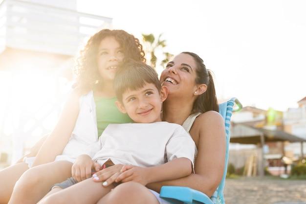 Счастливая семья среднего размера на пляже