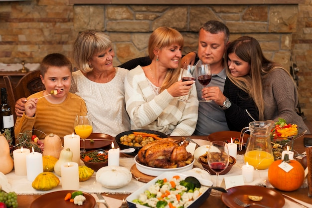 Счастливая семья среднего размера за ужином