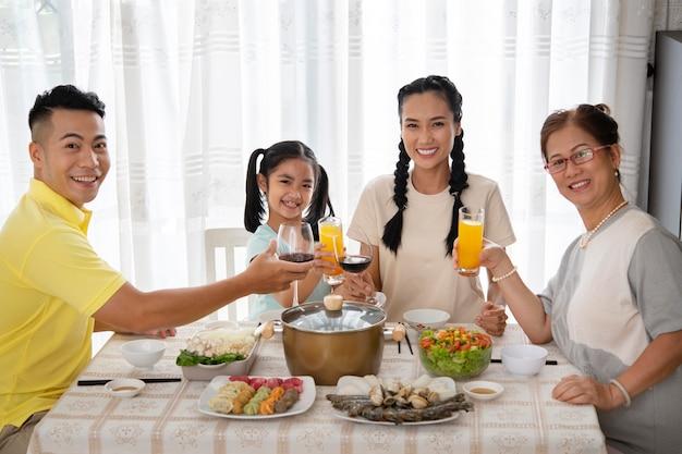 Счастливая семья среднего размера за столом