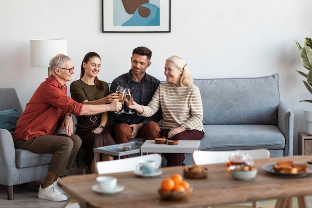 Medium shot happy family clinking glasses