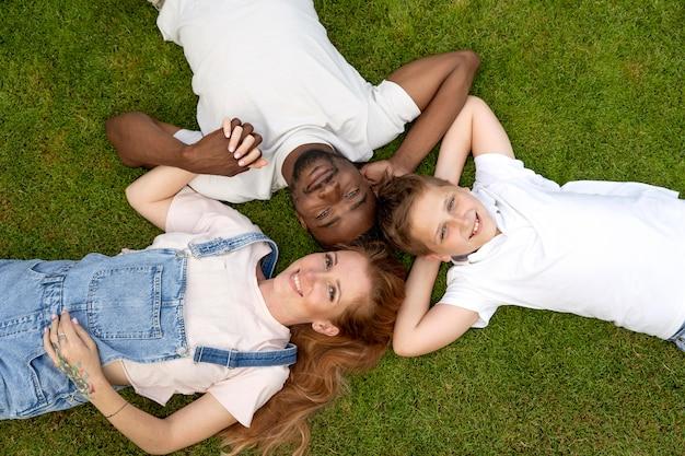 Medium shot happy family laying on grass