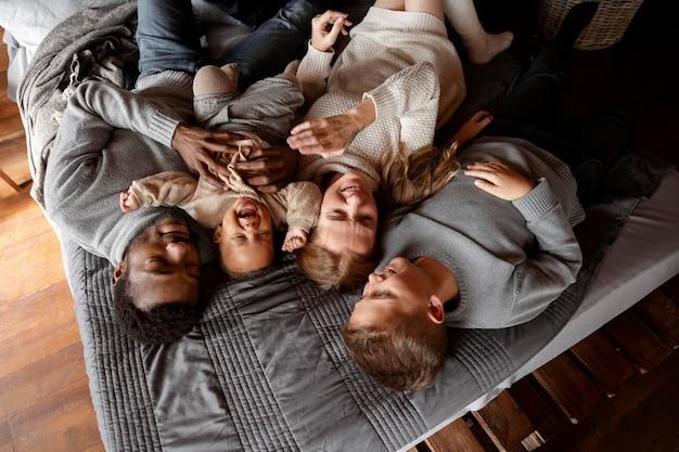 ベッドに横たわっているミディアムショットの幸せな家族