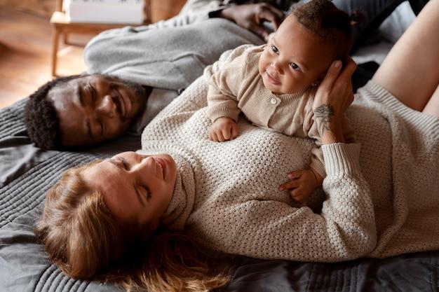 子供と一緒に横たわっているミディアムショットの幸せな家族