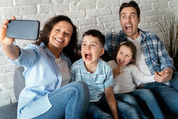 Medium shot happy family taking selfies