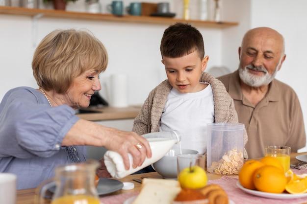 ミディアムショットの幸せな家族と食べ物