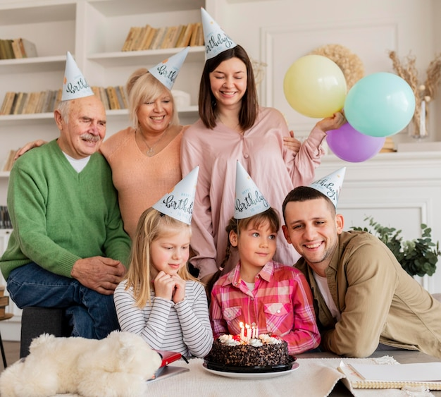 ミディアムショットの幸せな家族とパーティーハット