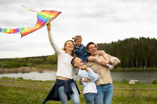 Medium shot happy family with rainbow kite