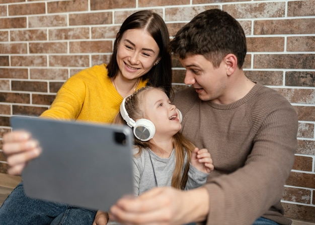 Medium shot happy family with tablet
