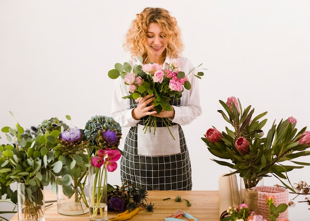 Medium shot happy florist looking at flowers