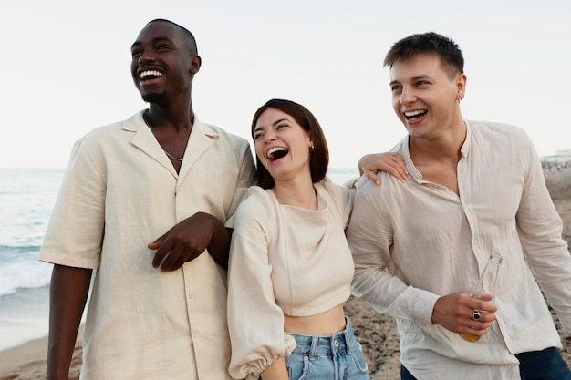 해변에서 중간 샷 행복한 친구들