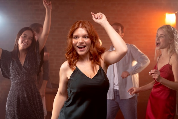 Medium shot happy friends dancing at club