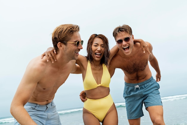Medium shot happy friends at seaside