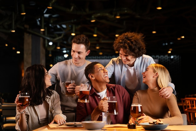 Amici felici del colpo medio che si siedono nel pub