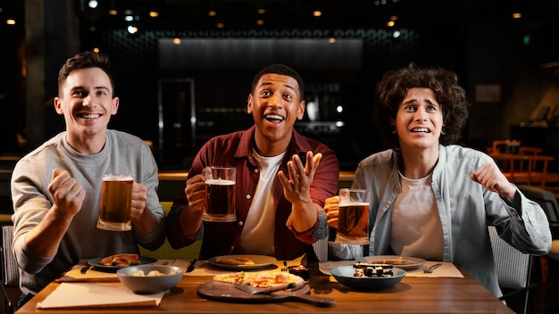 パブでビールとミディアムショットの幸せな友達