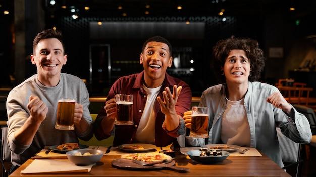 Amici felici del colpo medio con birra nel pub