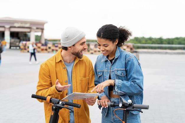 Средний снимок счастливых друзей со скутерами Бесплатные Фотографии