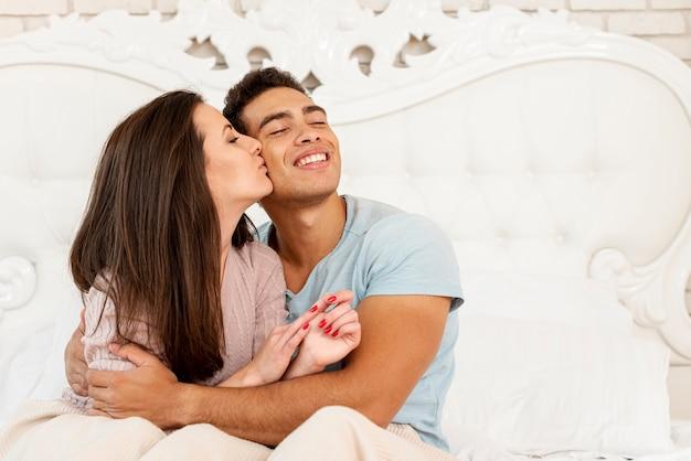 Medium shot happy girl kissing boyfriend